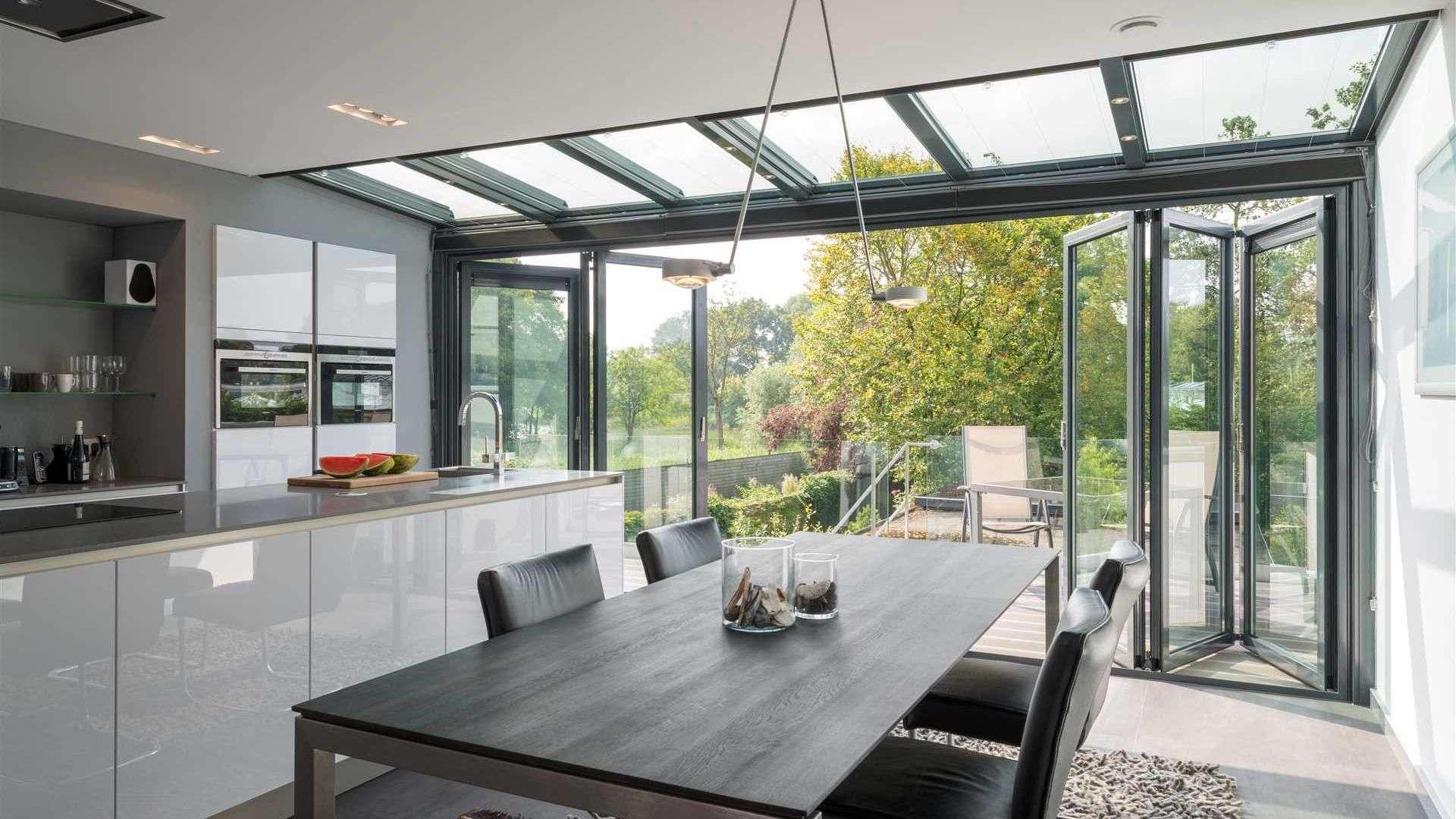 Innenansicht des Solarlux SDL Nobiles Wintergarten mit geöffneter Glasfront, Küchenzeile im Inneren und großen dunklem Holzesstisch im Vordergrund