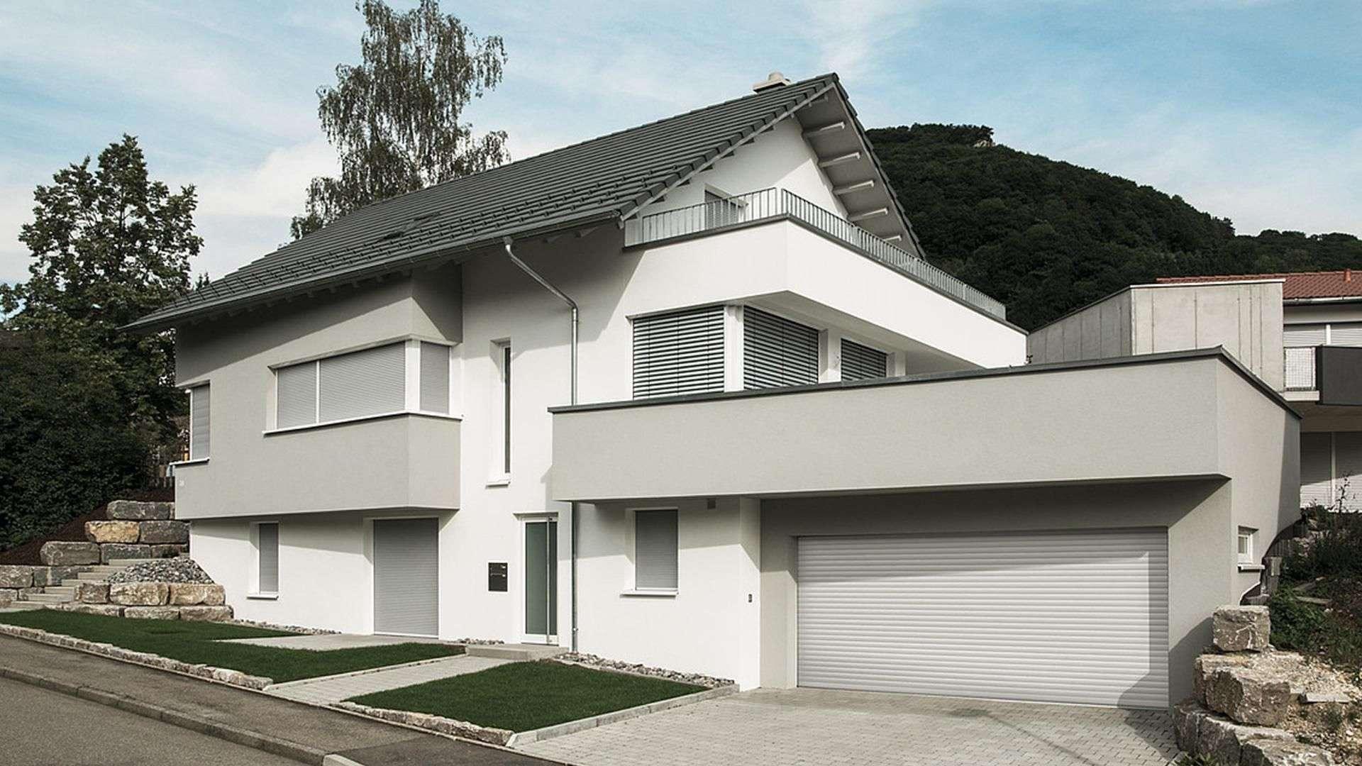 Wohnhaus mit vielen Fenstern mit Beschattung davor und großen Hof mit Garagentor