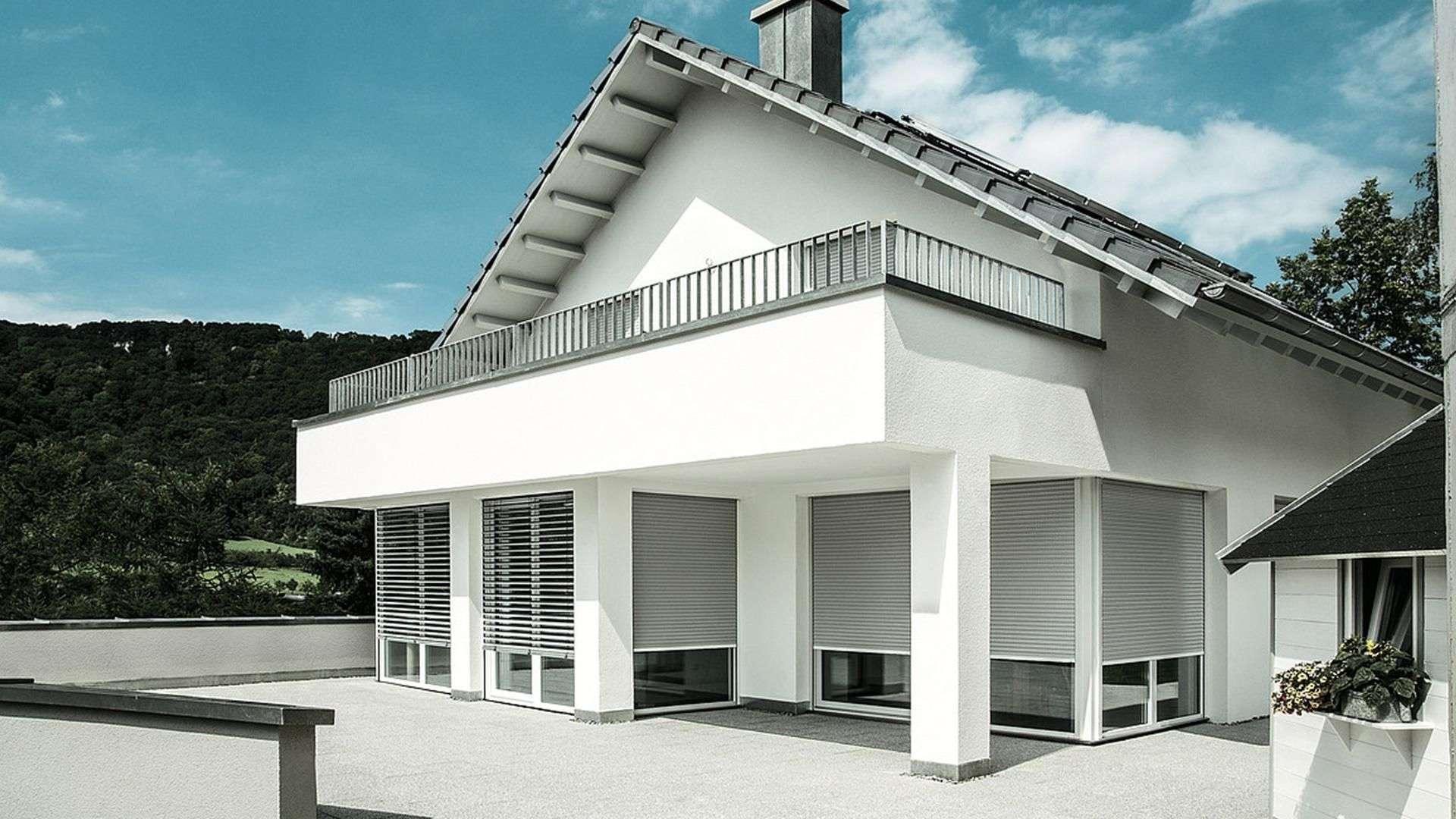 Wohnhaus mit bodentiefen Fenstern mit halb-runtergelassenen Rollläden