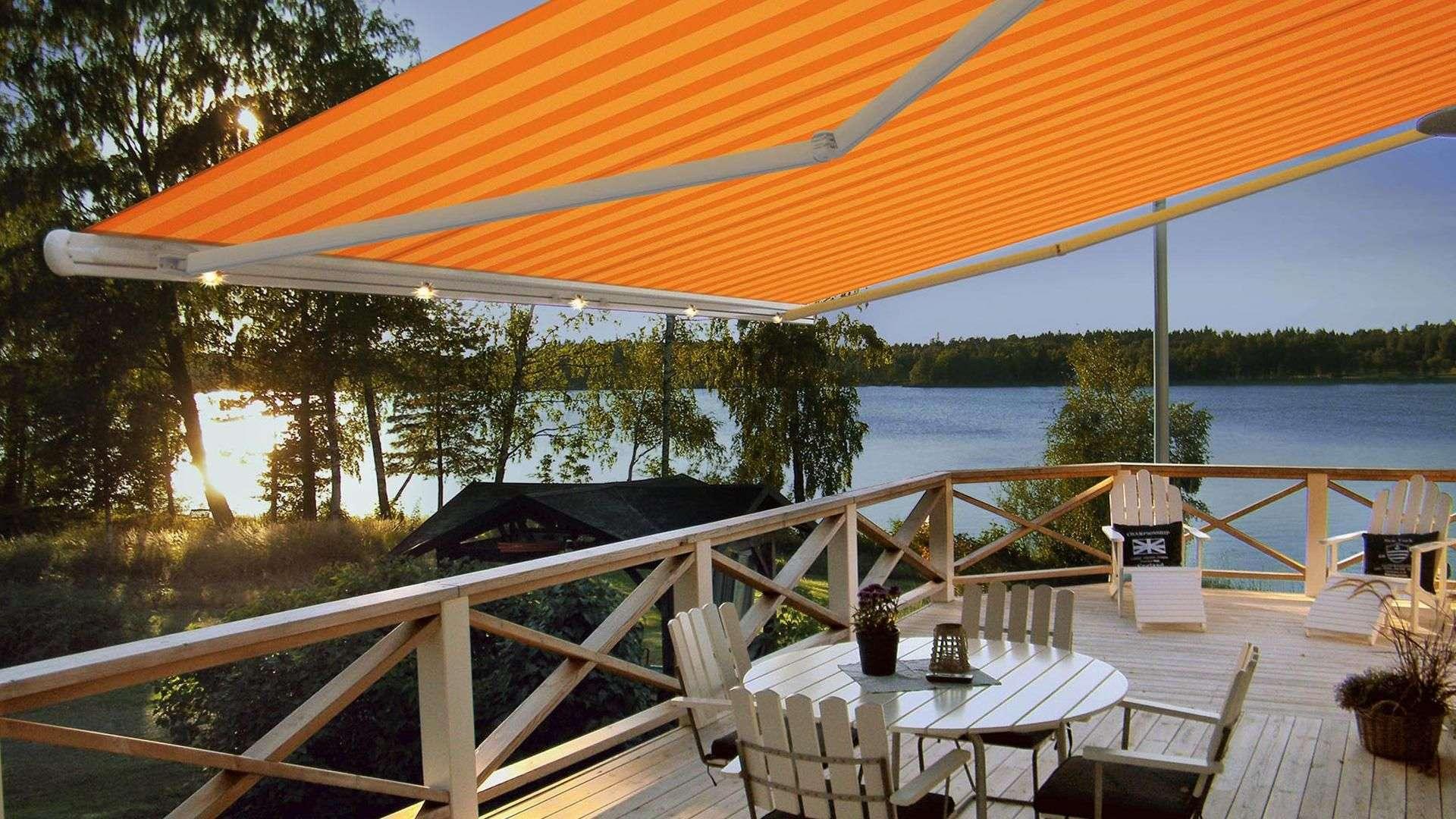 Blick unter eine orange Gelenkarm-Markise über einer Terrasse an einem See