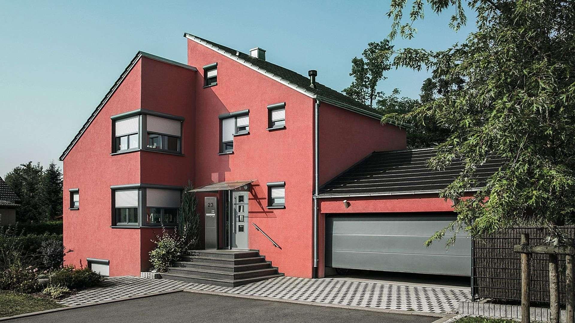 rotes Wohnhaus mit zwei Pultdächern, Garagentor und Beschattung vor den Fenstern