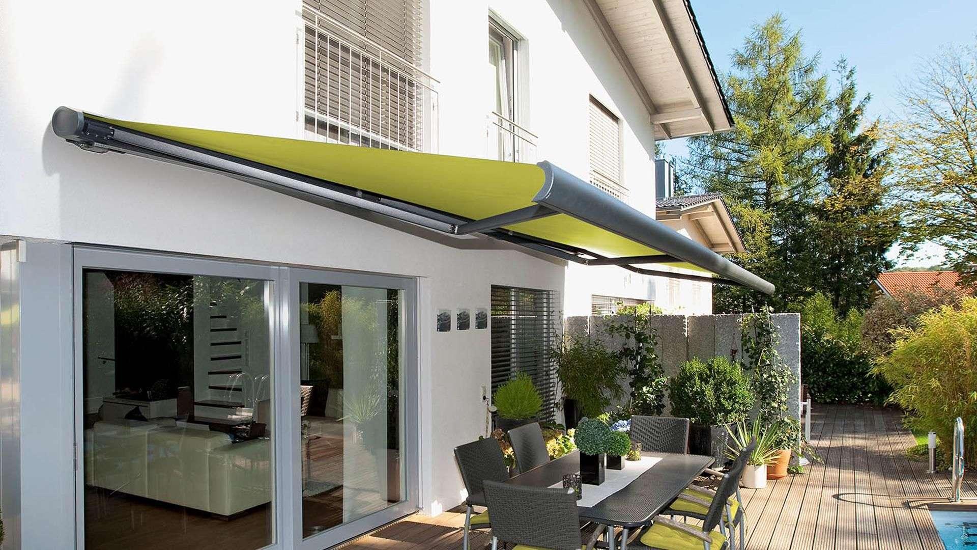 grüne Gelenkarm-Markise an einem weißen Wohnhaus mit Terrasse mit Esstisch