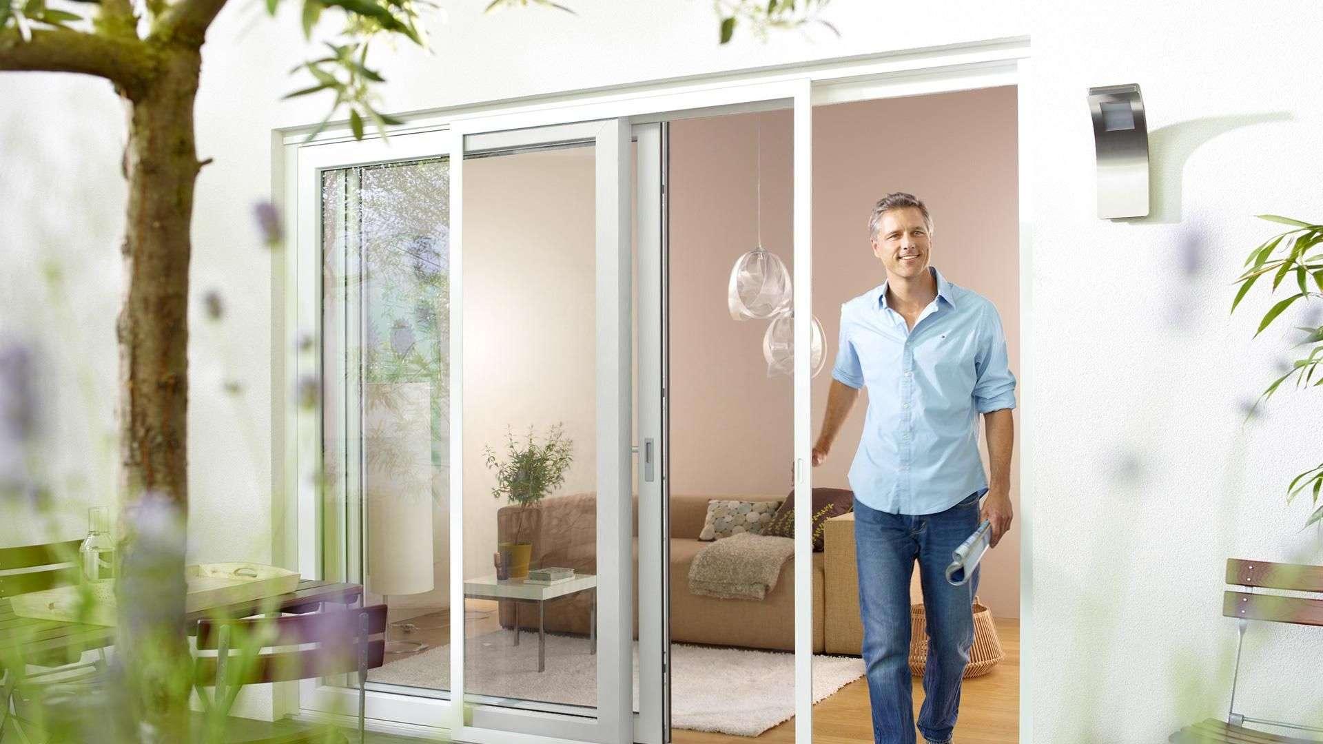 Mann kommt aus einer Terrassentür mit Insektenschutz-Gitter davor