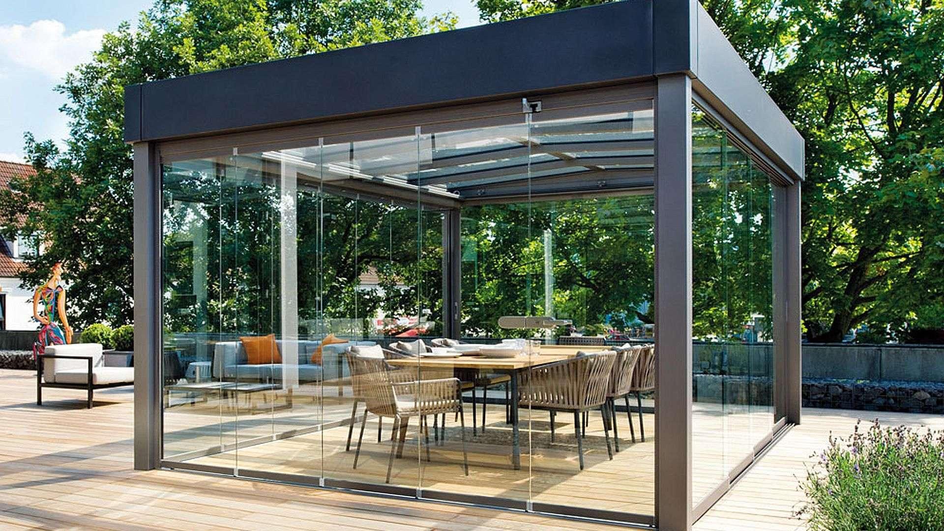 freistehendes Glashaus Atrium Carre in einem grünen Garten mit einem Esstisch in der Mitte