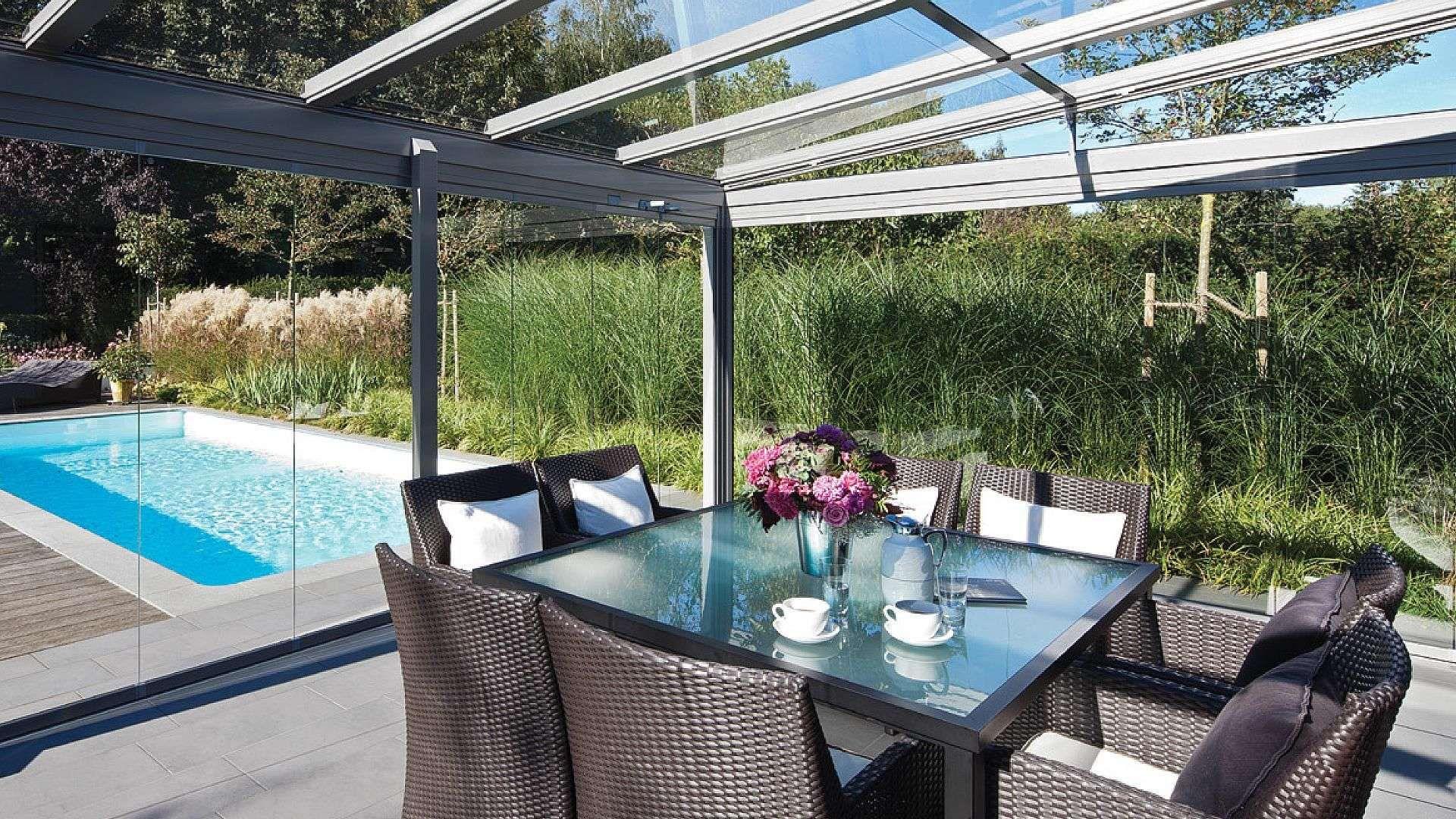 Innenansicht eines Glashaus mit Esstisch im Inneren und Blick auf den Garten mit Pool