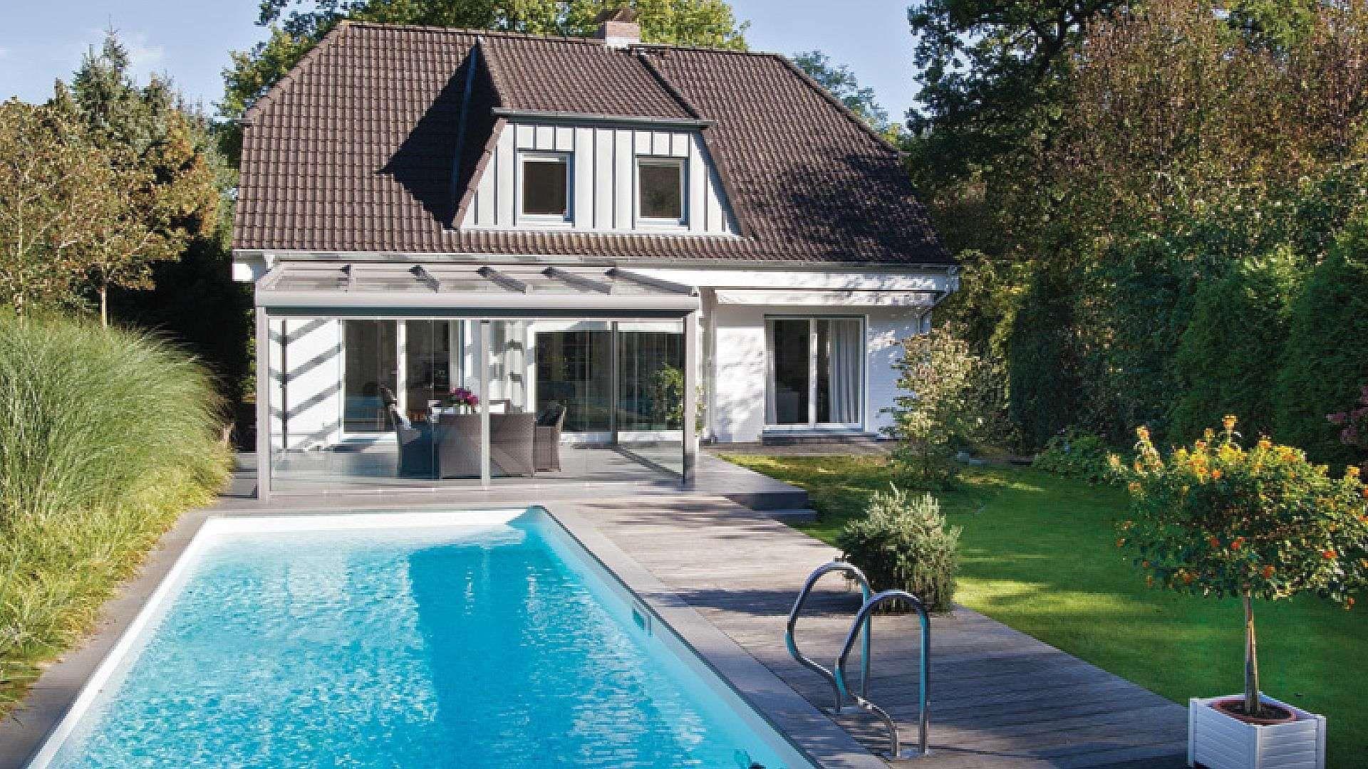 Wohnhaus mit Glashaus im Grünen und Pool im Vordergrund