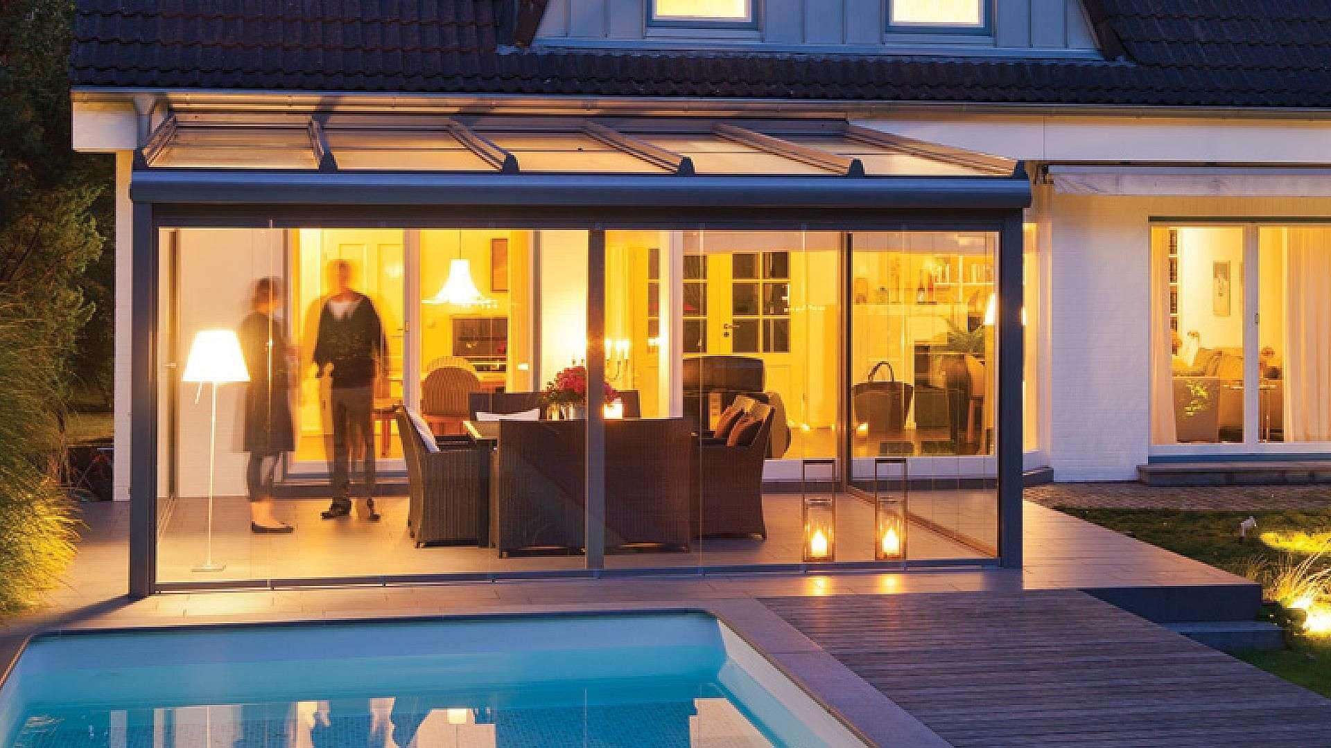 Haus mit Solarlux Wintergarten bei Dämmerung. Im Wintergarten stehen zwei Personen und im Vordergrund ist ein Pool.