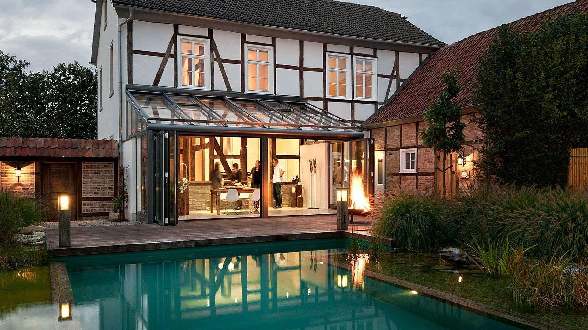 Fachwerkhaus mit Solarlux SDL Nobiles Wintergarten mit geöffneter Glasfront und großem Pool im Vordergrund bei Dämmerung