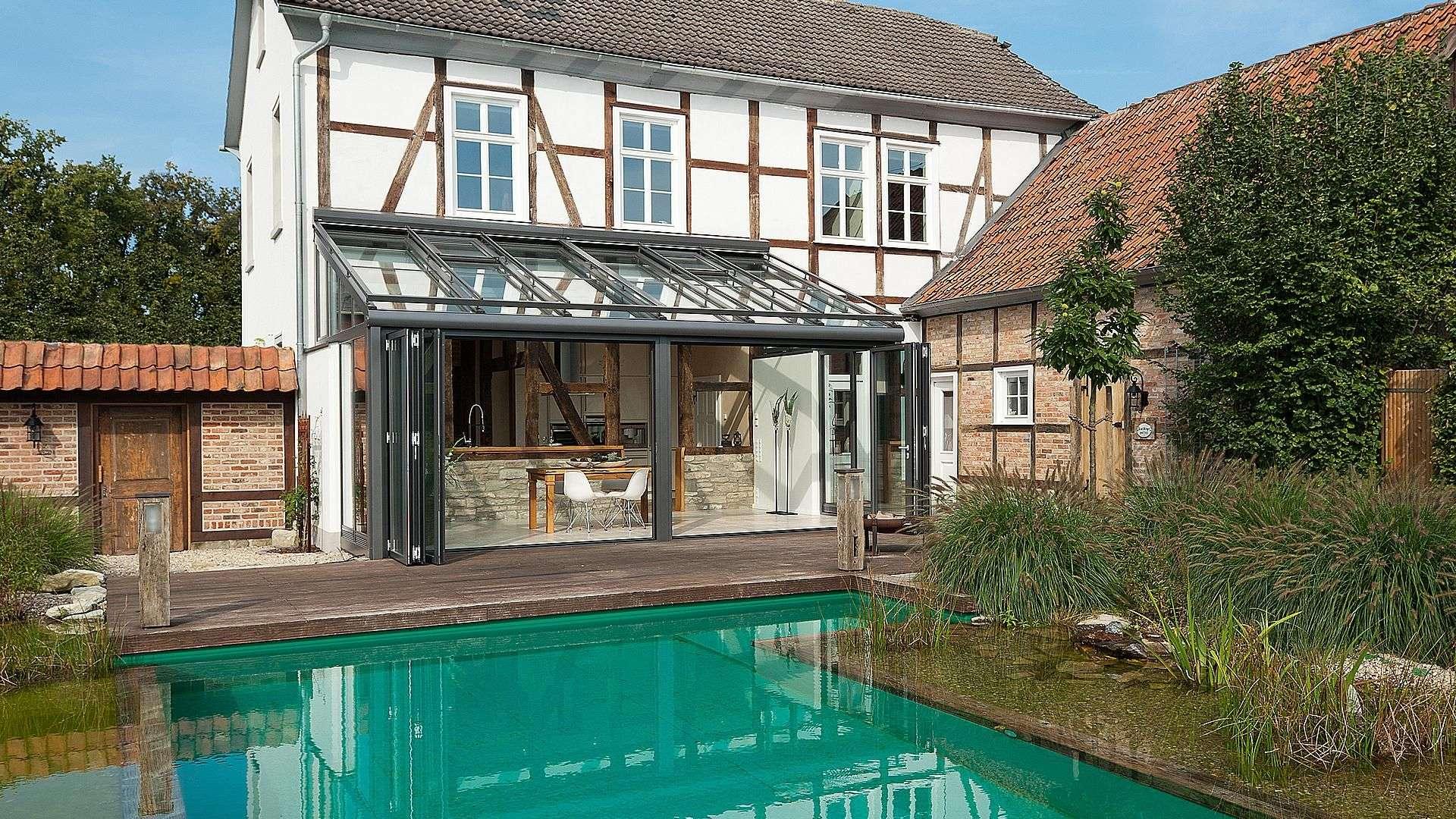 Fachwerkhaus mit Solarlux SDL Nobiles Wintergarten mit geöffneter Glasfront und großem Pool im Vordergrund