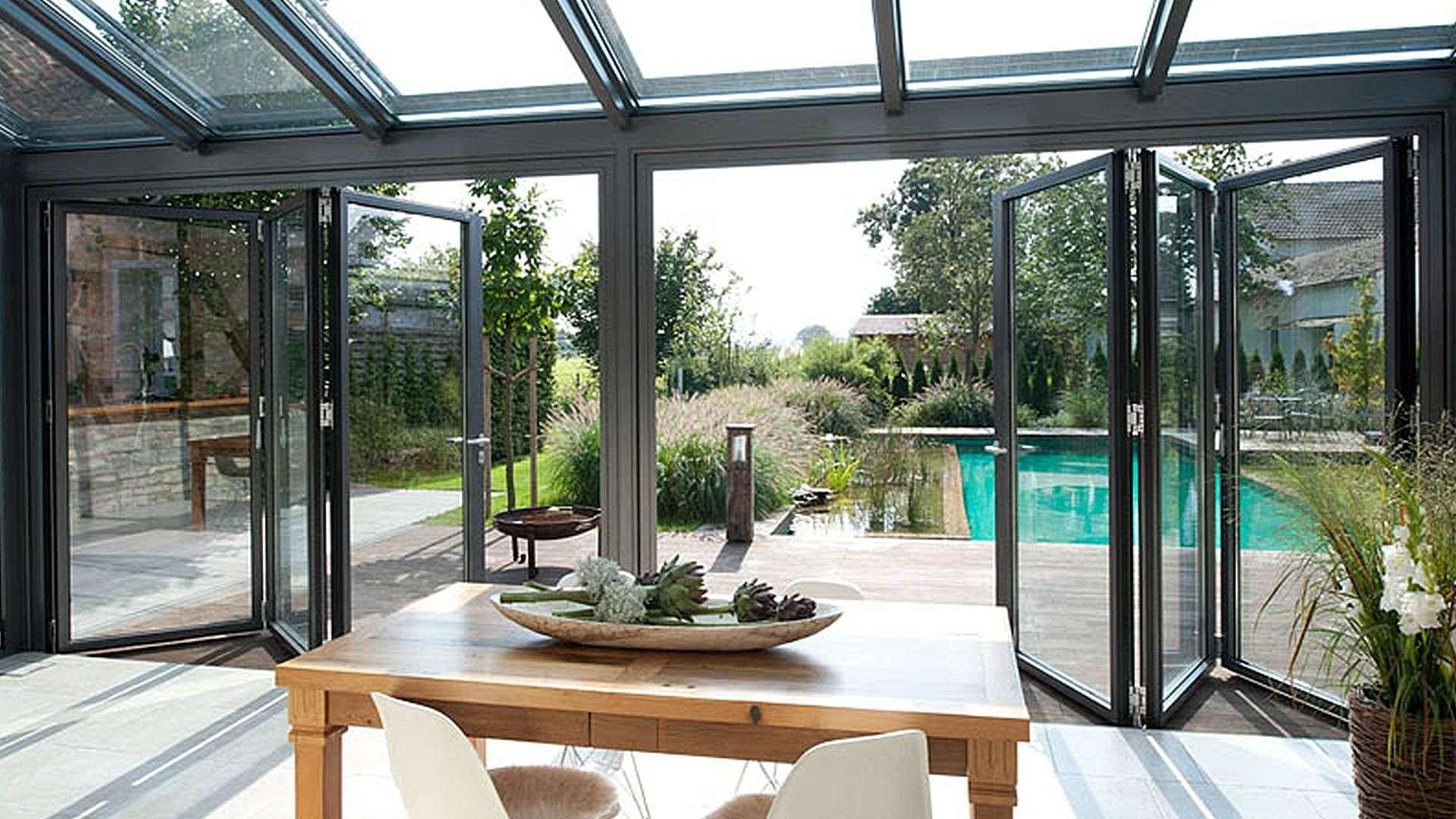 Innenansicht eines Solarlux SDL Nobiles Wintergartens mit geöffneter Glasfront mit Blick auf einen Pool und Esstisch im Inneren des Wintergartens