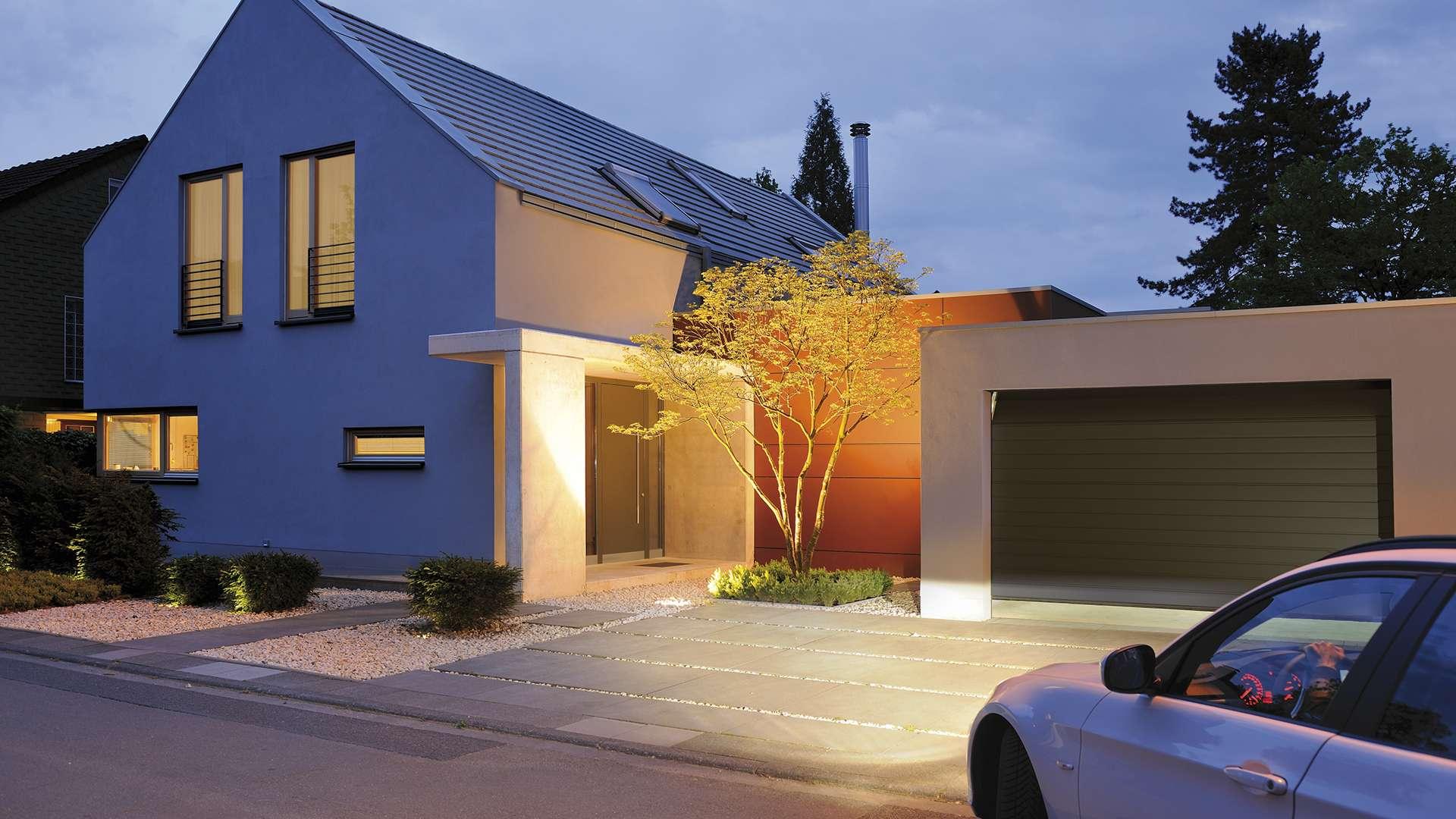 Modernes Wohnhaus mit Sektional-Garagentor bei Dämmerung